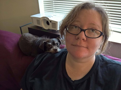 A photo of a woman wearing glasses, sitting on a couch, with a small dog resting his head on her shoulder.